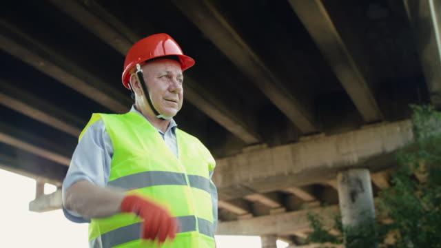 Happy senior railroader in uniform looking into distance and correcting helmet video