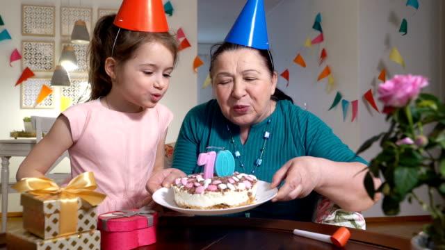 lycklig senior kvinna och hennes lilla barnbarn som blåser ut tårta ljus till spindelväv kamera medan firar födelsedag med sin familj via videochatt. - birthday celebration looking at phone children bildbanksvideor och videomaterial från bakom kulisserna