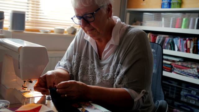 Happy Senior Woman Doing a Hobby Sewing A Quilt video