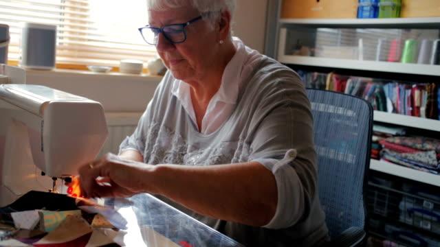 vídeos de stock e filmes b-roll de mulher idosa feliz dando um passatempo costura um acolchoado - edredão