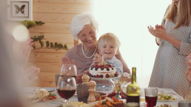 glad senior kvinna med födelsedagsfest hemma med familj - birthday celebration looking at phone children bildbanksvideor och videomaterial från bakom kulisserna