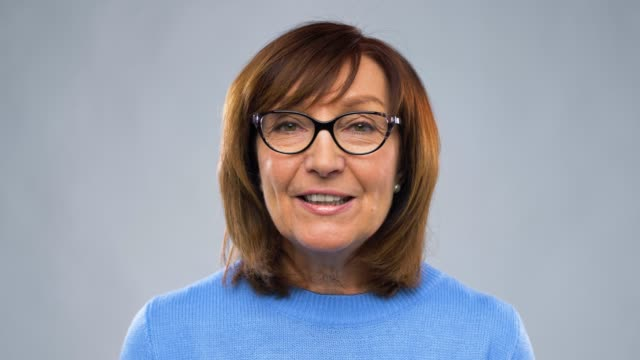 happy senior woman having video chat or interview communication, age and people concept - happy senior woman in glasses having video chat or interview over grey background interview event stock videos & royalty-free footage