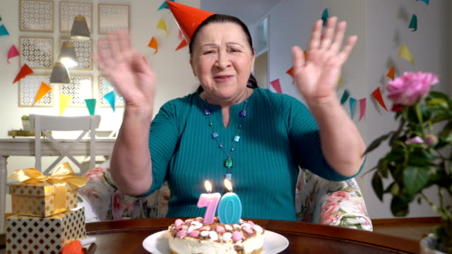 lycklig senior kvinna hålla tårta till kamera medan firar födelsedag med familjen via videochatt - birthday celebration looking at phone children bildbanksvideor och videomaterial från bakom kulisserna