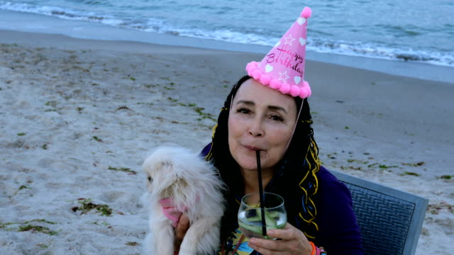 Happy senior woman in a birthday cap with her dog - a white Pekingese.