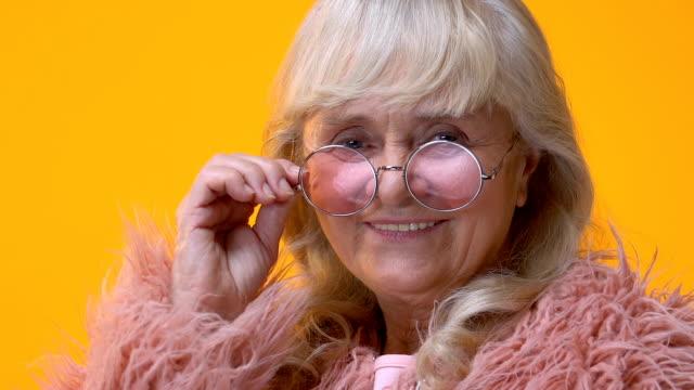 vídeos de stock e filmes b-roll de happy senior woman in stylish eyeglasses winking on bright background, flirt - piscar