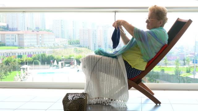 Happy senior woman knitting  in nursing home. video