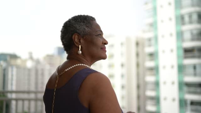vídeos de stock, filmes e b-roll de mulher idosa feliz olhando para a vista na varanda do apartamento - consciência negra