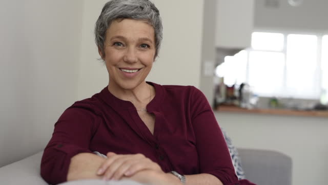 Happy senior woman smiling on couch Portrait of smiling senior woman relaxing on couch at home. Happy mature woman sitting on sofa and looking at camera. Closeup of lady relaxing at home. mid adult women stock videos & royalty-free footage