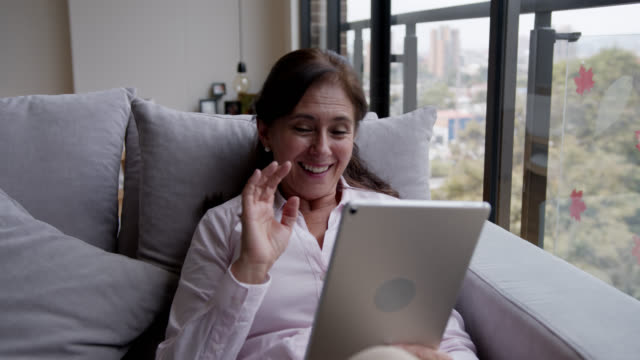 Happy senior woman staying safe at home on a video conference using a tablet Happy senior woman staying safe at home on a video conference using a tablet - Flatten the curve stay at home stay home stock videos & royalty-free footage