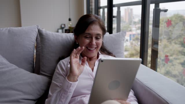 vídeos y material grabado en eventos de stock de feliz mujer mayor que se mantiene a salvo en casa en una videoconferencia usando una tableta - stay home