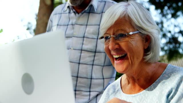 Happy senior woman using laptop in garden 4k video