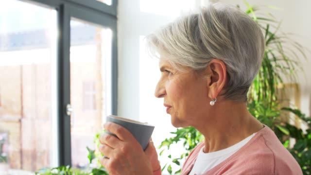 lycklig äldre kvinna med kopp te hemma video