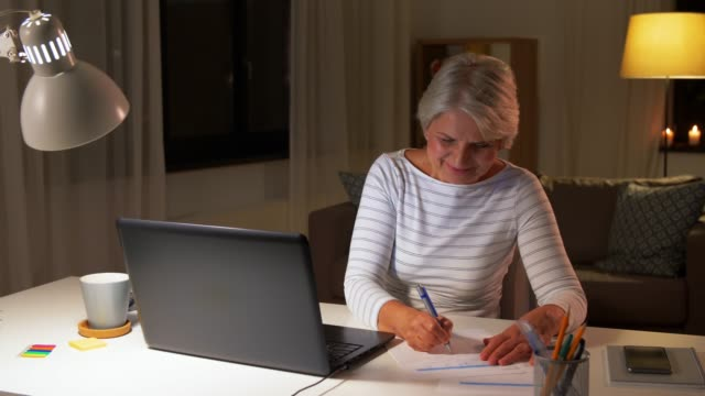 happy senior woman with laptop at home in evening technology, old age and people concept - happy senior woman with laptop filling tax form at home in evening form filling stock videos & royalty-free footage