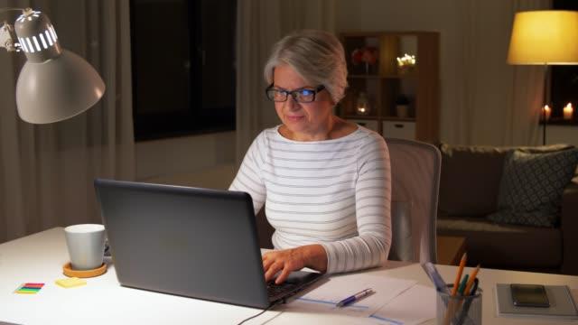 donna anziana felice con laptop a casa la sera - donne mature video stock e b–roll
