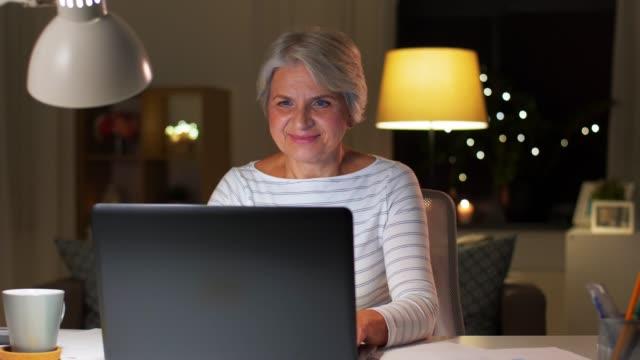 glad äldre kvinna med laptop hemma på kvällen video