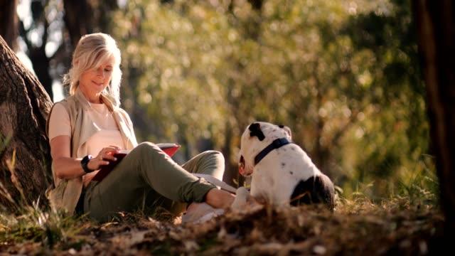 lycklig senior kvinna med hund läsebok i park - senior walking bildbanksvideor och videomaterial från bakom kulisserna