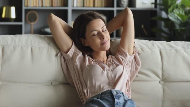 vidéos et rushes de salon serein heureux de jeune femme sur le sofa avec des yeux fermés - se reposer