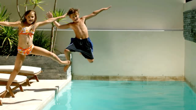 Happy siblings diving into the swimming pool video