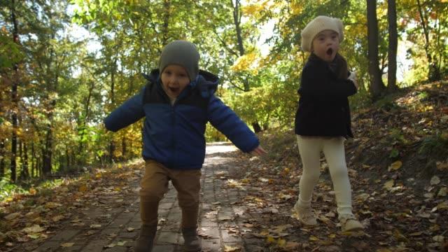 遊び中に公園の道に沿って走っている幸せな兄弟 - disabilitycollection点の映像素材/bロール