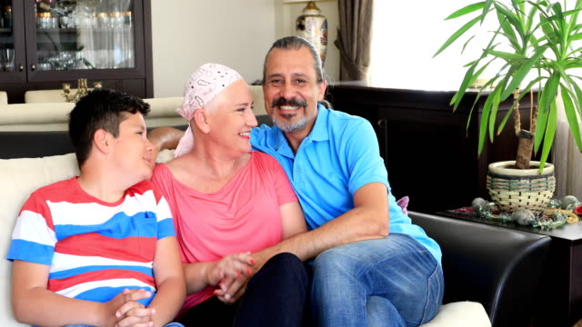 Happy sick woman with husband and son Portrait of a happy sick woman fight with cancer with family's help cancer patient stock videos & royalty-free footage