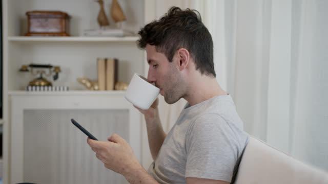 vídeos de stock, filmes e b-roll de feliz solteiro em casa relaxando no sofá curtindo um café enquanto mandava mensagens no smartphone - café bebida