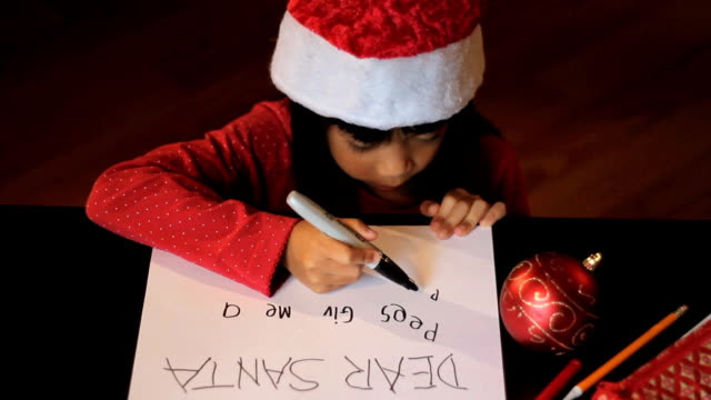 Happy Six Year Old Girl Writing Santa Claus A happy six year old Asian girl writes a special letter to Santa Claus at Christmas.  See more CHRISTMAS clips here! note message stock videos & royalty-free footage