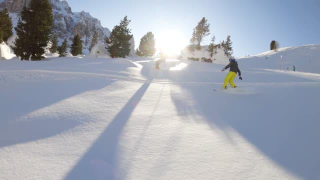 stockvideo's en b-roll-footage met volg close up: gelukkige skiër en snowboarder die plezier hebben met het skiën in backcountry op een zonnige winterdag in besneeuwde bergen. extreme freeride skiër die verse poedersneeuw van in bergskitoevlucht in dolomieten italië berijdt - sneeuwkap