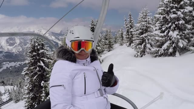 happy skier climbs up the chair lift to the mountain top and shows her thumb up - sci video stock e b–roll