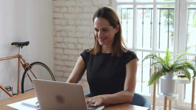 Happy skilled caucasian businesswoman working on computer.
