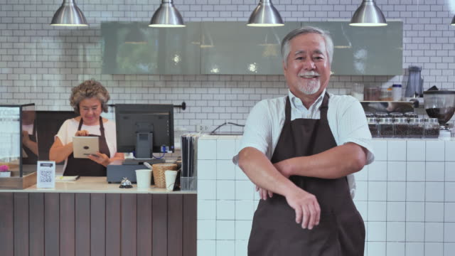 Happy small business owner standing at front of bar with Wife in background preparing coffee.