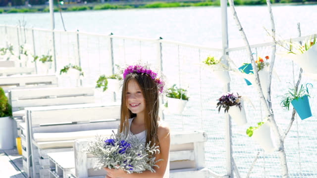 Happy smart girl admiring with flowers and smiling. Slowly video