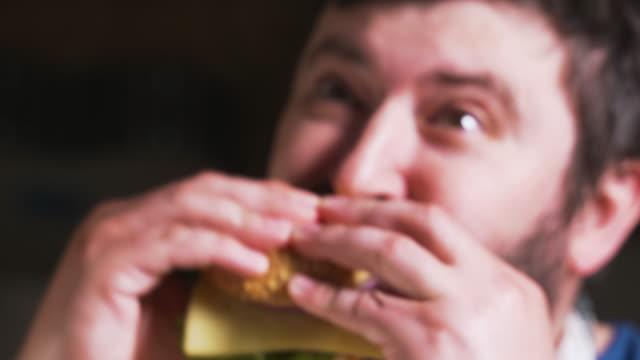 felice uomo sorridente con barba che mangia una deliziosa carne di hamburger con formaggio e verdure. il giovane affamato che ha impilato hamburger al bar si diverte a mangiare, masticare. primo tempo - antipasto video stock e b–roll