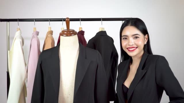 Feliz sonriente mujer asiática de confección diseñadores con maniquí maniquí y chaquetas de traje en muchos colores en suspensión - vídeo