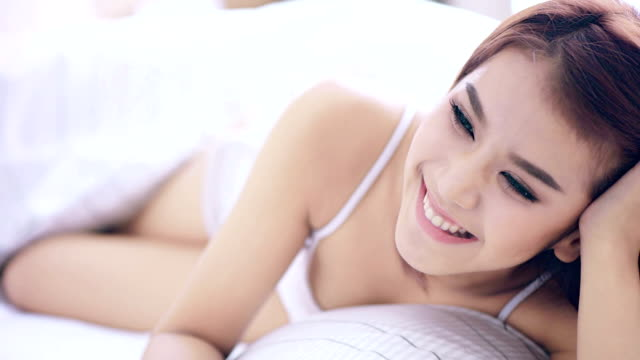 Happy smiling beautiful woman awaking with cup of coffee at bedroom video