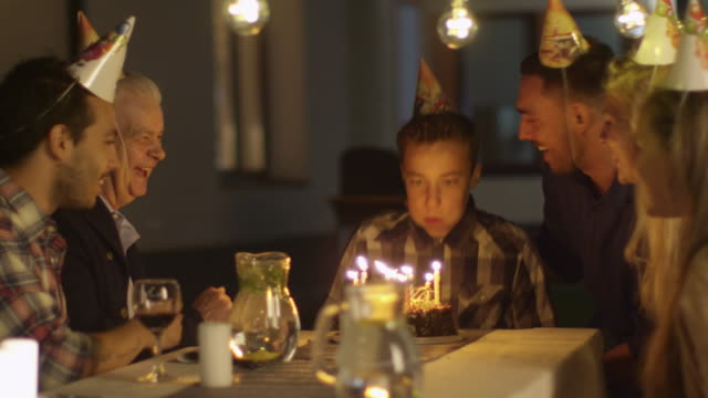 Happy Smiling Boy Blowing Candles out on her Birthday Cake. The Boy Surrounded by His Family and Friends video