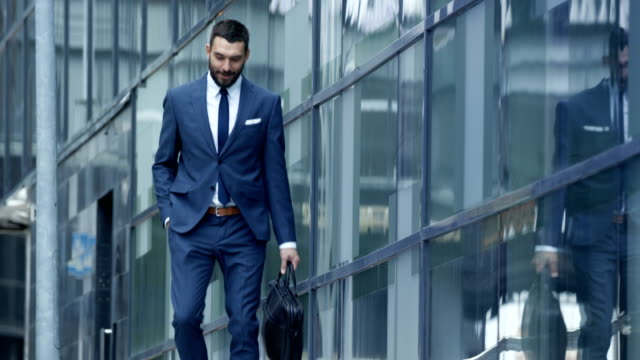 Happy Smiling Business Man with a Bag Goes Down the Stairs and Checks His Smartphone, He's in the Business District. Happy Smiling Business Man with a Bag Goes Down the Stairs and Checks His Smartphone, He's in the Business District. Shot on RED EPIC-W 8K Helium Cinema Camera. handsome people stock videos & royalty-free footage