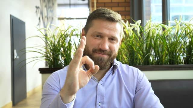 happy smiling businessman shows ok at camera, portrait, in cafe, steadycam shot - znak ok filmów i materiałów b-roll