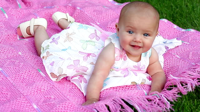 happy smiling cheerful baby girl on pink blanket in park video