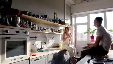 vídeos y material grabado en eventos de stock de una feliz sonriente pareja de jóvenes es enjoyin la soleada mañana en la cocina sentado en las encimeras y hablar - desayuno
