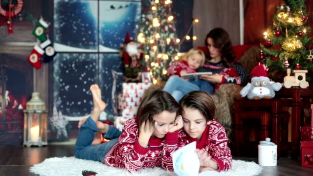 幸せな笑顔の家族、お母さん、お父さんと3人の男の子、クリスマス休暇のために自宅で家族の肖像画を持っています - サンタの帽子点の映像素材/bロール