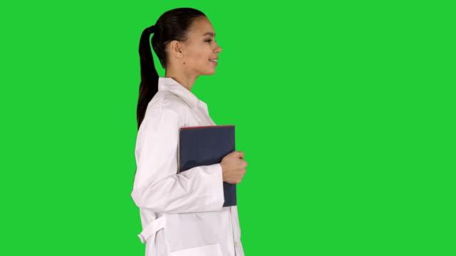 vidéos et rushes de heureux docteur femelle de sourire marchant retenant des cahiers ou des documents sur un écran vert, chroma key - bloc note