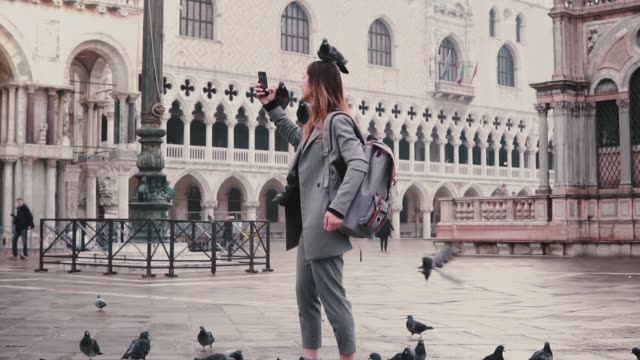 Happy smiling female tourist with pigeons sitting on her arm and head takes selfie on city square in Venice slow motion.