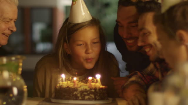 Happy Smiling Girl Blowing Candles out on her Birthday Cake Mädchen umringt von Familie und Freunden – Video