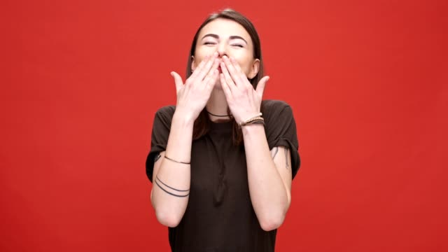 ммHappy smiling girl greeting by waving her hand and sending air kisses isolated over red background video