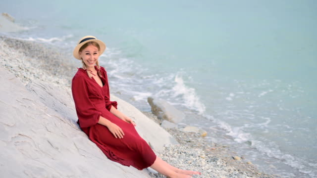 A happy smiling girl in a red summer dress and a straw hat sits on a rocky shore and looks at the horizon of the sea. He waves his hands, drawing attention to himself.