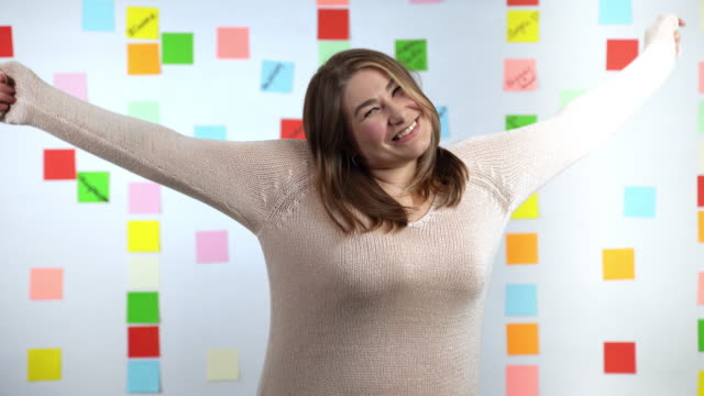 Happy smiling girl in casual clothes, overweight problem in modern society. Attractive young brunette woman gesturing positively on colorful stickers background, ambitions and success concept
