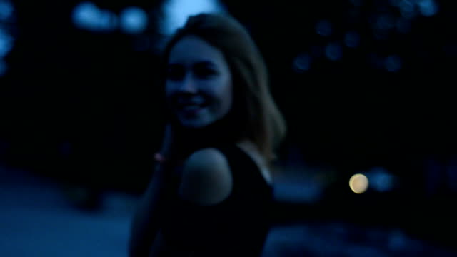 happy smiling girl looks into the camera and walks late at night on the street video