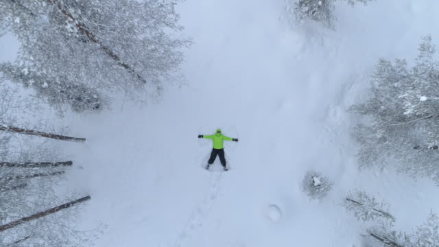 AERIAL: Happy smiling girl making snow angles in fresh snow on snowy mountain video