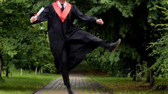 Happy smiling graduate walking in park with diploma, jumping with excitement video