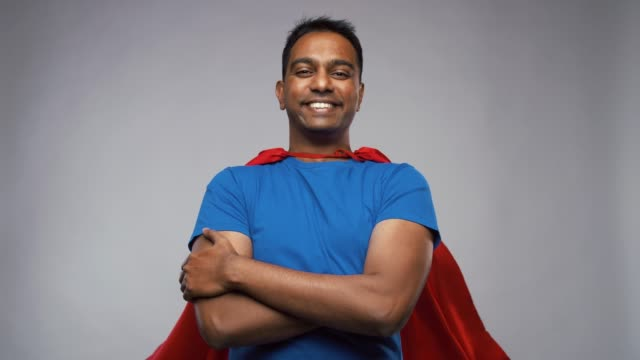 happy smiling indian man in red superhero cape super power and people concept - happy smiling indian man in red superhero cape with crossed arms over grey background cape garment stock videos & royalty-free footage